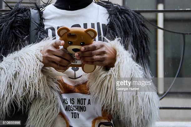 Niki Sha seen at Skylight at Moynihan Station outside the Jeremy Scott show wearing Moschino outfit with teddy bear phone case during New York...