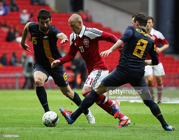 Niki Zimling of Denmark gets past Luke Wilkshire and Mile Jedinak of Australia during the International Friendly between Denmark and Australia at...