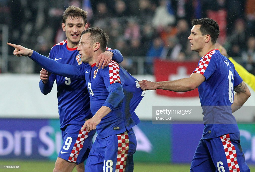 Nikica Jelavic of Croatia (L) and Dejan Lovren of Croatia (R) celebrate the goal (1:1) of Ivica Olic of Croatia (C) during the international friendly match between Switzerland and Croatia at the AFG Arena on March 5, 2014 in St Gallen, Switzerland.