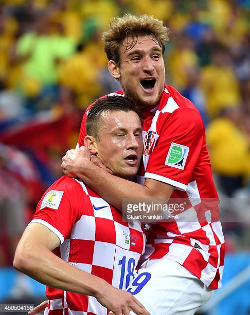 Nikica Jelavic of Croatia celebrates with team-mate Ivica Olic of Croatia after his shot came off Marcelo of Brazil to score an own goal during the...