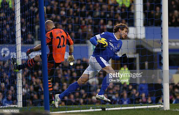 Nikica Jelavic of Everton runs out the goal with the ball as Aston Villa keeper Brad Guzan kicks the post in frustration after Marouane Fellaini of...