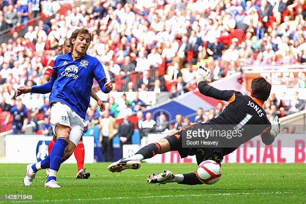Nikica Jelavic of Everton shoots past Brad Jones of Liverpool to score their first goal during the FA Cup with Budweiser Semi Final match between...