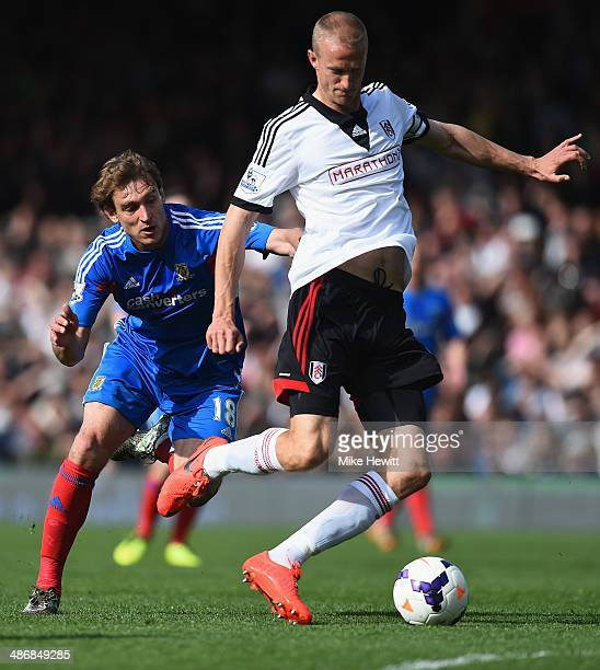 Nikica Jelavic of Hull challenges Brede Hangeland of Fulham during the Barclays Premier League match between Fulham and Hull City at Craven Cottage...