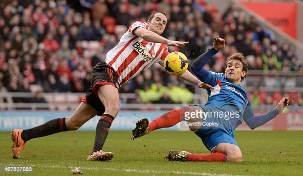 Nikica Jelavic of Hull City and John O'Shea of Sunderland battle for the ball during the Premier League match between Sunderland and Hull City at...