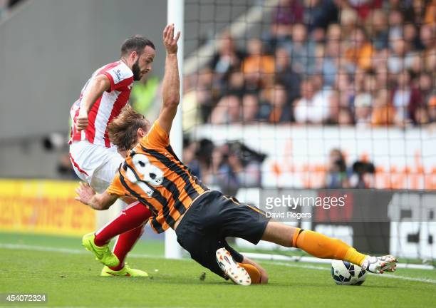Nikica Jelavic of Hull City slips the ball past Marc Wilson to score the first goal during the Barclays Premier League match between Hull City and...