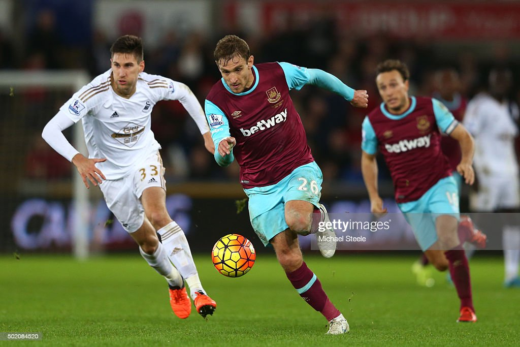 Nikica Jelavic of West Ham is pursued by Federico Fernandez of Swansea City during the Barclays Premier League match between Swansea City and West Ham United at the Liberty Stadium on December 20, 2015 in Swansea, Wales.