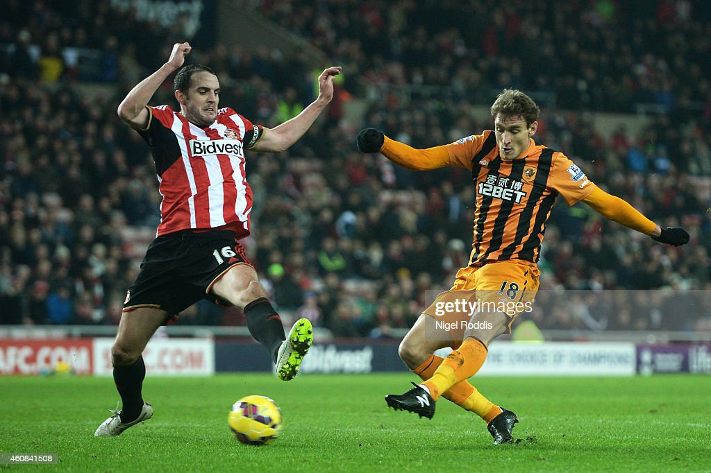 Nikica Jelevic of Hull City scores his team's third goal despite the efforts of John O'Shea of Sunderland during the Barclays Premier League match between Sunderland and Hull City at the Stadium of Light on December 26, 2014 in Sunderland, England.