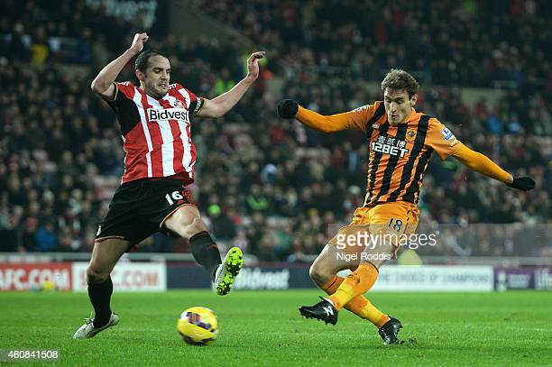 Nikica Jelevic of Hull City scores his team's third goal despite the efforts of John O'Shea of Sunderland during the Barclays Premier League match...