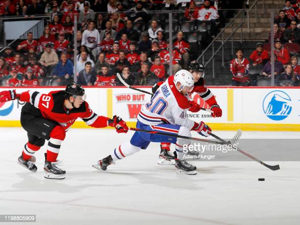 Nikita Gusev and Damon Severson of the New Jersey Devils skate after Joel Armia of the Montreal Canadiens as he controls the puck during the second...