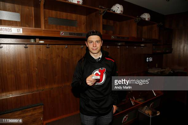 Nikita Gusev of the New Jersey Devils displays the puck with which he scored his first NHL goal during the game against the Winnipeg Jets on October...