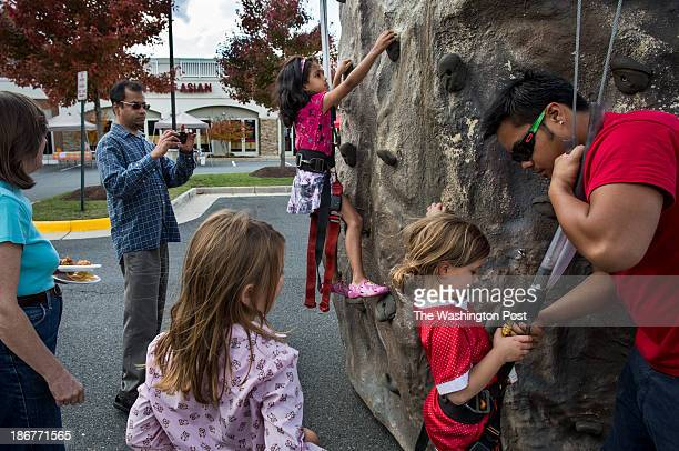 Nikita Iyer climbs a rock wall at the first annual fall festival at the Heritage Hunt shopping center in Gainesville, VA, November 2013, while her...