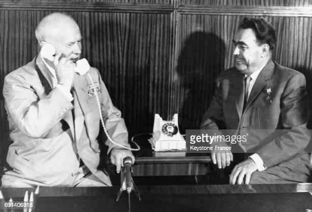 Nikita Khrouchtchev et Leonid Brejnev au téléphone avec les astronautes Andrian Nikolaev et Pavel Popovich afin de les féliciter de leur voyage de...