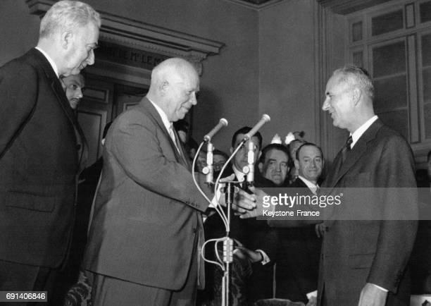 Nikita Khrouchtchev serre la main à Gaston Defferre maire de Marseille dont il est l'invité d'honneur durant son tour de France en présence de Louis...