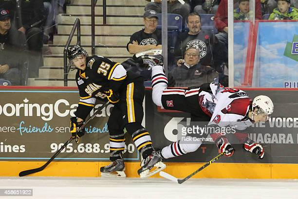 Nikita Korostelev of the Sarnia Sting lays a hip check on Graham Knott of the Niagara IceDogs at the Meridian Center on November 8 2014 in St...
