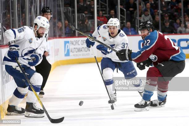 Nikita Kucherov and Yanni Gourde of the Tampa Bay Lightning battle for the puck against Colin Wilson of the Colorado Avalanche at the Pepsi Center on...