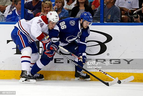 Nikita Kucherov of the Tampa Bay Lightning and Alexei Emelin of the Montreal Canadiens battle for the puck at the Tampa Bay Times Forum on April 1...