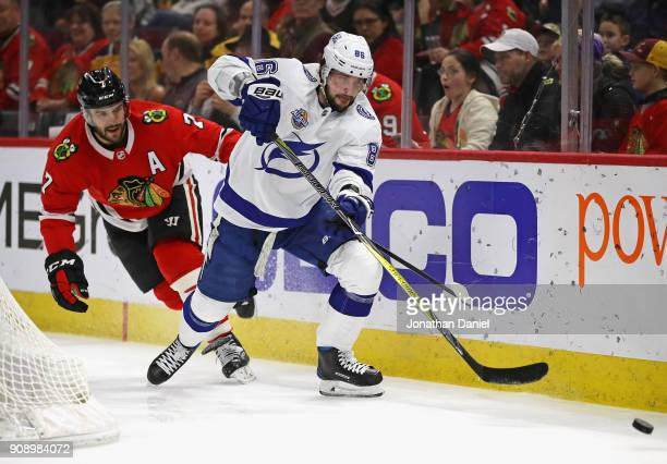 Nikita Kucherov of the Tampa Bay Lightning and Brent Seabrook of the Chicago Blackhawks chase down the puck at the United Center on January 22 2018...