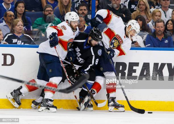 Nikita Kucherov of the Tampa Bay Lightning battles against Keith Yandle and Alex Petrovic of the Florida Panthers during the third period at Amalie...