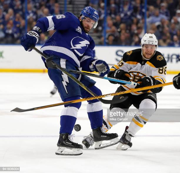 Nikita Kucherov of the Tampa Bay Lightning battles David Pastrnak of the Boston Bruins for a loose puck during the second period of the game at the...