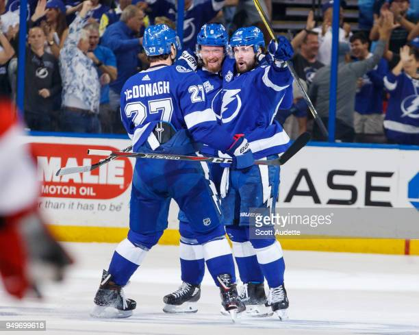 Nikita Kucherov of the Tampa Bay Lightning celebrates his game winning and series clinching goal with teammates Anton Stralman and Ryan McDonagh and...