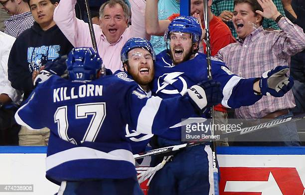 Nikita Kucherov of the Tampa Bay Lightning celebrates with his teammate Nikita Nesterov and Alex Killorn after scoring the game winning goal in...