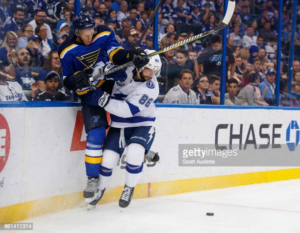Nikita Kucherov of the Tampa Bay Lightning checks Carl Gunnarsson of the St Louis Blues during the third period at Amalie Arena on October 14 2017 in...