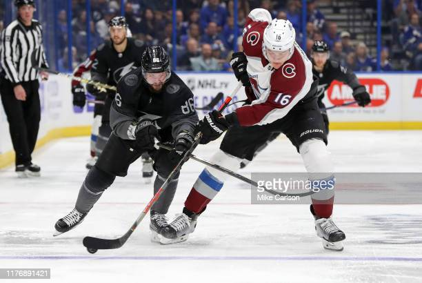 Nikita Kucherov of the Tampa Bay Lightning checks Nikita Zadorov of the Colorado Avalanche during the second period at the Amalie Arena on October 19...