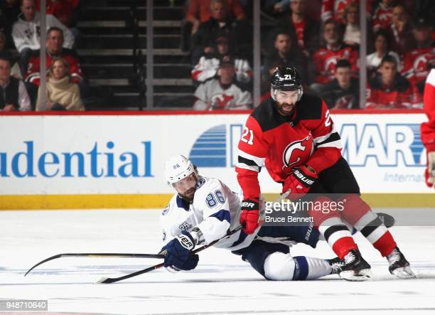 Nikita Kucherov of the Tampa Bay Lightning is checked by Kyle Palmieri of the New Jersey Devils in Game Four of the Eastern Conference First Round...