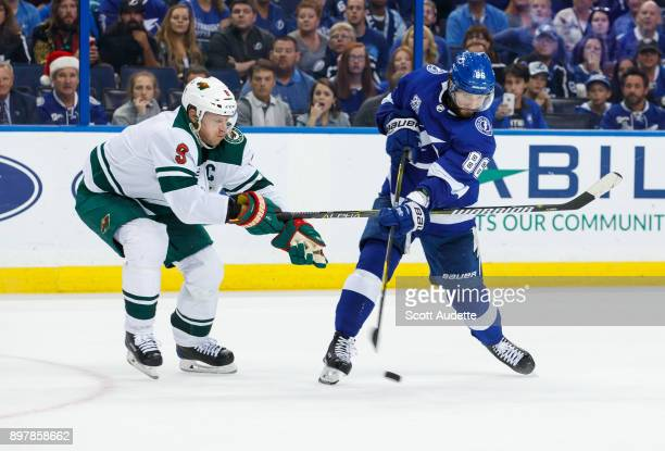 Nikita Kucherov of the Tampa Bay Lightning shoots against Mikko Koivu of the Minnesota Wild during the third period at Amalie Arena on December 23...