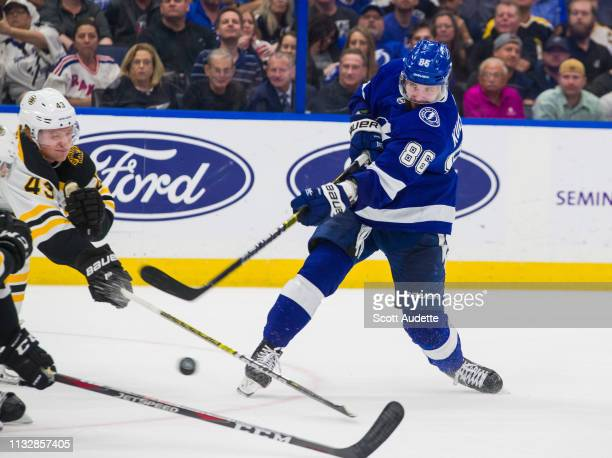 Nikita Kucherov of the Tampa Bay Lightning shoots the puck against Danton Heinen of the Boston Bruins during the third period at Amalie Arena on...