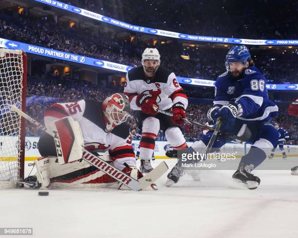Nikita Kucherov of the Tampa Bay Lightning skates against goalie Cory Schneider and Andy Greene of the New Jersey Devils in Game Five of the Eastern...