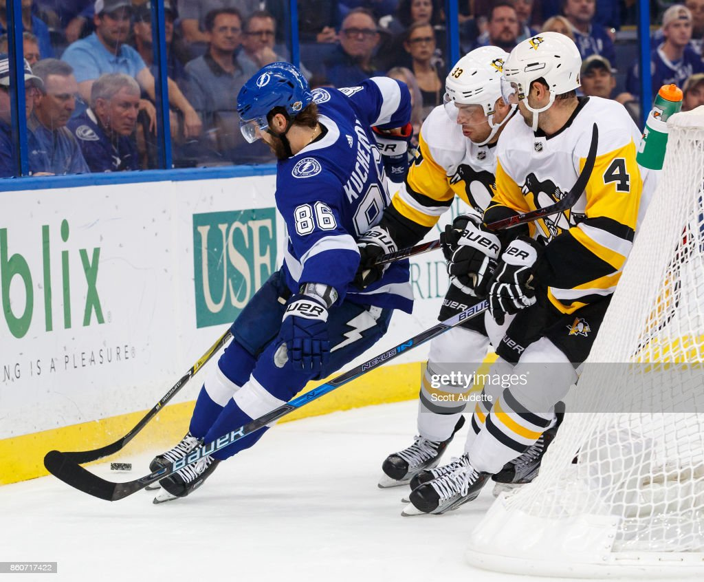 Nikita Kucherov #86 of the Tampa Bay Lightning skates against Greg McKegg #33 and Justin Schultz #4 of the Pittsburgh Penguins during the third period at Amalie Arena on October 12, 2017 in Tampa, Florida.