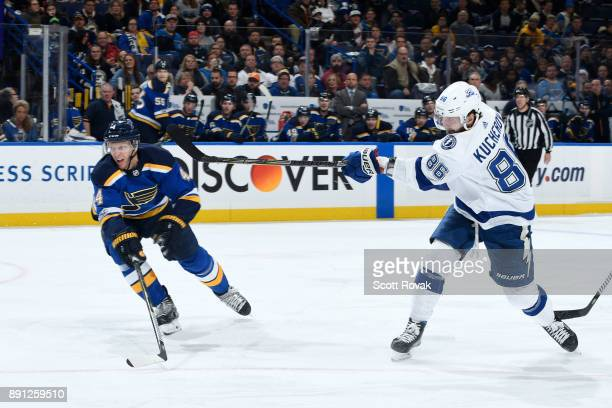 Nikita Kucherov of the Tampa Bay Lightning takes a shot as Carl Gunnarsson of the St Louis Blues defends at Scottrade Center on December 12 2017 in...