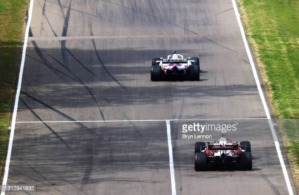 Nikita Mazepin of Russia driving the Haas F1 Team VF-21 Ferrari and Kimi Raikkonen of Finland driving the Alfa Romeo Racing C41 Ferrari on track...