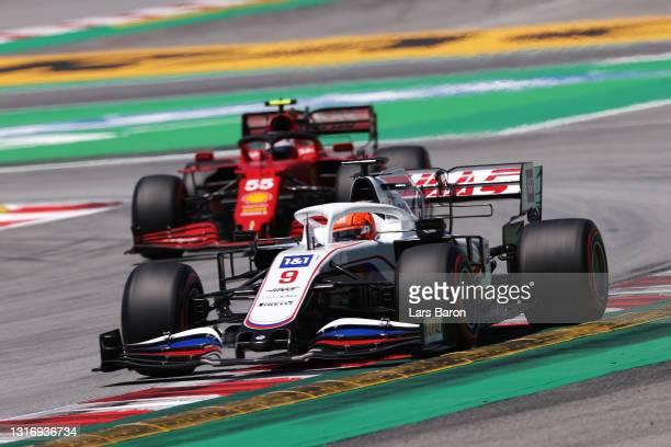 Nikita Mazepin of Russia driving the Haas F1 Team VF-21 Ferrari leads Carlos Sainz of Spain driving the Scuderia Ferrari SF21 during final practice...