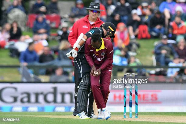 Nikita Miller of the West Indies fields the ball off his own bowling and runs into Tom Latham of New Zealand during the One Day International match...