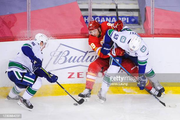 Nikita Nesterov of the Calgary Flames battles Nils Hoglander and Bo Horvat of the Vancouver Canucks during an NHL game at Scotiabank Saddledome on...