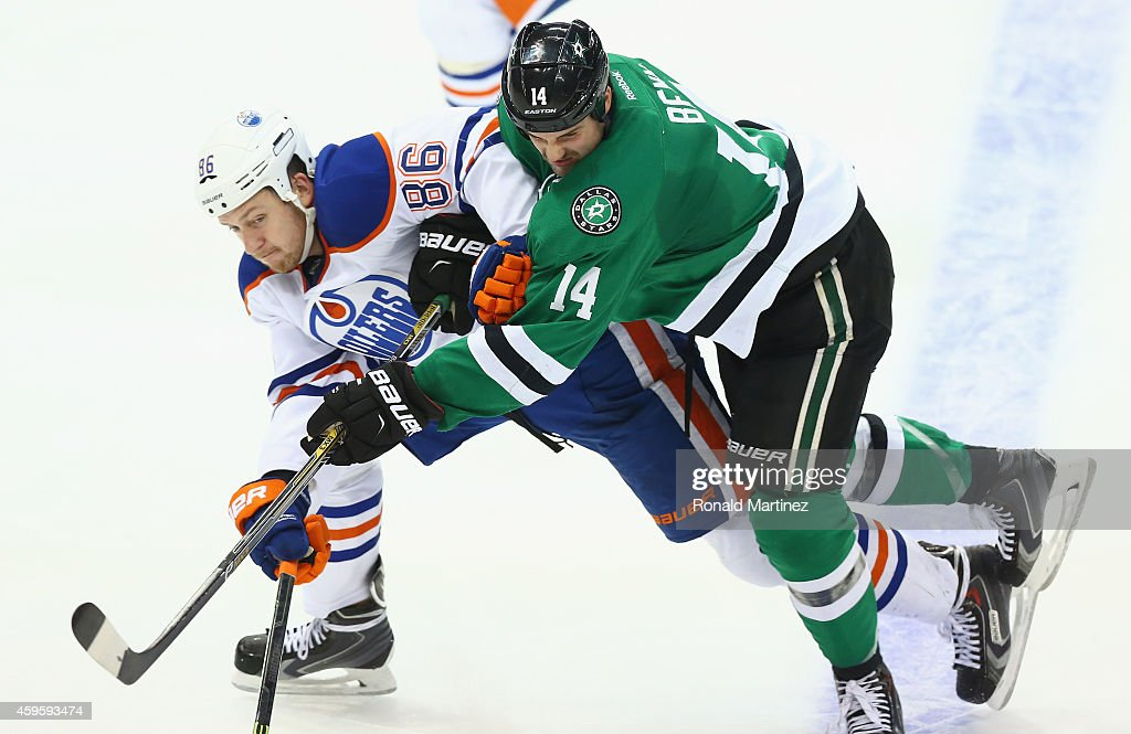 Nikita Nikitin #86 of the Edmonton Oilers and Jamie Benn #14 of the Dallas Stars skate for the puck in the third period at American Airlines Center on November 25, 2014 in Dallas, Texas.