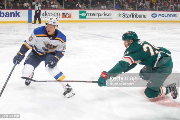Nikita Soshnikov of the St Louis Blues and Matt Dumba of the Minnesota Wild skate to the puck during the game at the Xcel Energy Center on February...