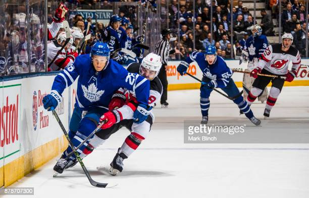 Nikita Soshnikov of the Toronto Maple Leafs battles for the puck with Will Butcher of the New Jersey Devils during the third period at the Air Canada...