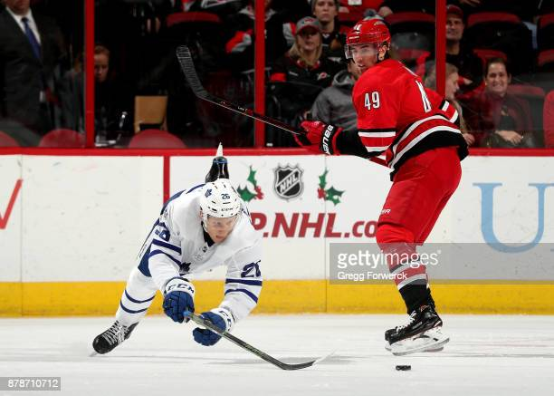 Nikita Soshnikov of the Toronto Maple Leafs dives toward a loose puck as Victor Rask of the Carolina Hurricanes looks on during an NHL game on...