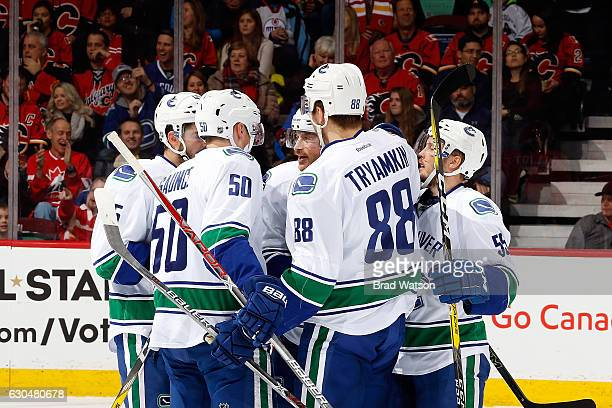 Nikita Tryamkin and teammates of the Vancouver Canucks celebrate a goal against the Calgary Flames during an NHL game on December 23 2016 at the...