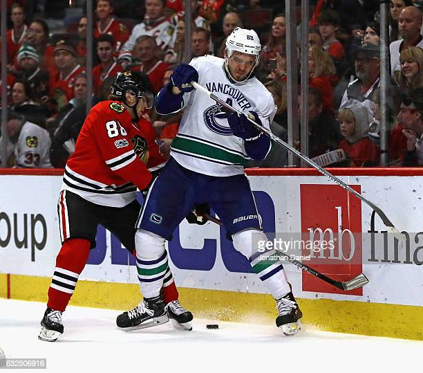 Nikita Tryamkin of the Vancouver Canucks and Patrick Kane of the Chicago Blackhawks battle for the puck at the United Center on January 22 2017 in...