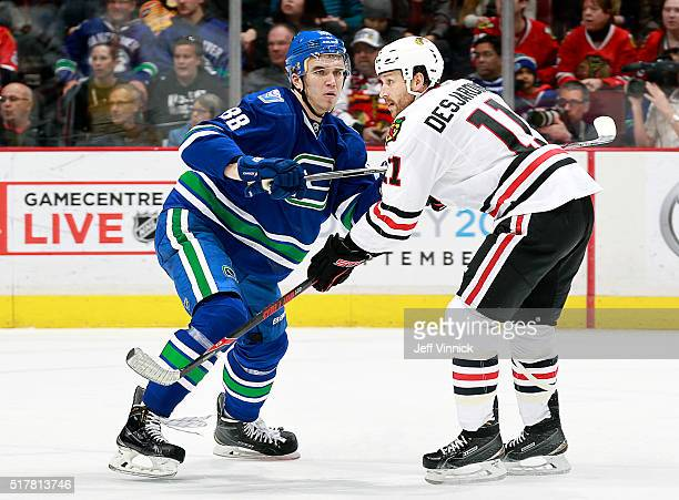 Nikita Tryamkin of the Vancouver Canucks checks Andrew Desjardins of the Chicago Blackhawks during their NHL game at Rogers Arena March 27 2016 in...