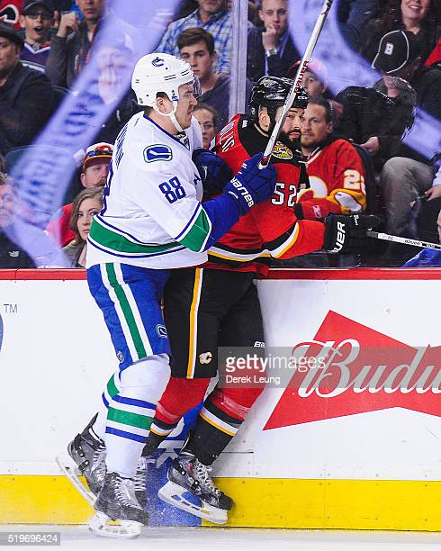 Nikita Tryamkin of the Vancouver Canucks checks Brandon Bollig of the Calgary Flames during an NHL game at Scotiabank Saddledome on April 7 2016 in...