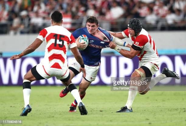 Nikita Vavilin of Russia is tackled by William Tupou of Japan and Pieter Labuschagne of Japan during the Rugby World Cup 2019 Group A game between...