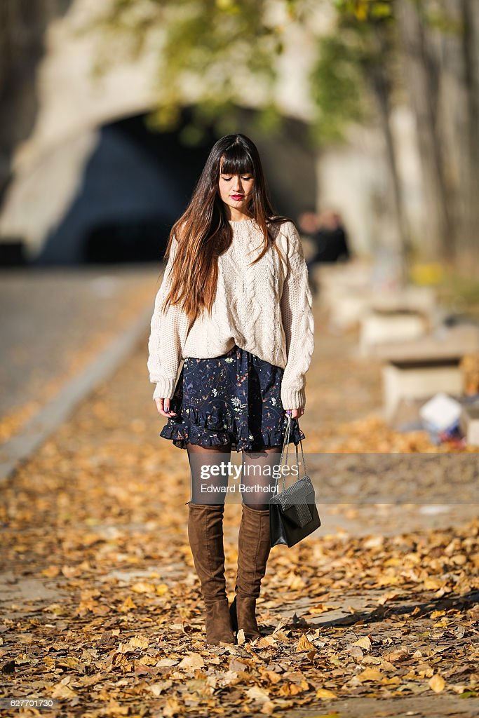 Nikita Wong, fashion and life style blogger @meetmeinparee, is wearing a Vero Moda dark blue skirt wih floral print, a Charlise white pull over, Zara brown suede boots, and a Saint Laurent bag, on December 4, 2016 in Paris, France.