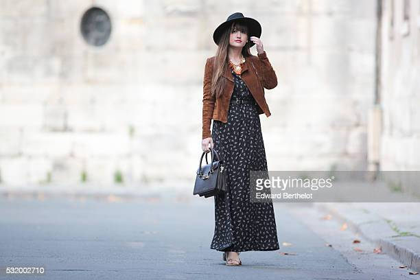 Nikita Wong , is wearing a Sisley black and white dress, Just Fab shoes, an Ilex black bag, and an H&M black hat, during a street style session, on...