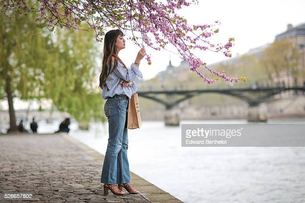 Nikita Wong is wearing Diabless blue jeans a Chicwish striped top an Improbable bag with the inscription I'm not Kate I'm not Cara Just me and Texto...