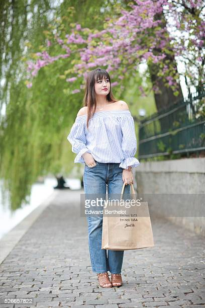 Nikita Wong is wearing Diabless blue jeans a Chicwish striped top an Improbable bag with the inscription 'I'm not Kate I'm not Cara Just me' and...